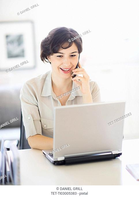 Woman working on laptop and talking on phone