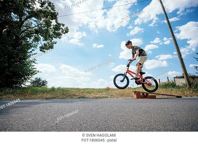 Boy riding bicycle off ramp
