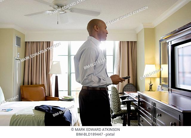 African businessman in hotel watching television