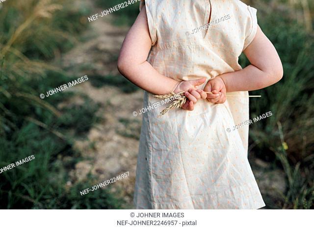 Girl holding stem behind her back