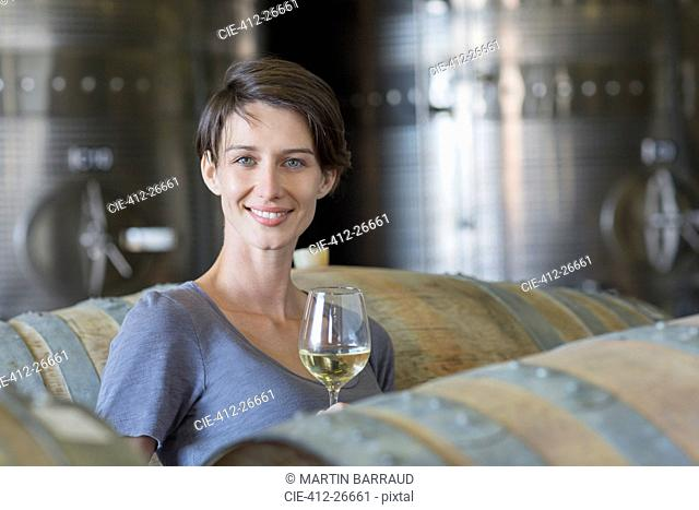 Portrait confident vintner drinking white wine in winery cellar
