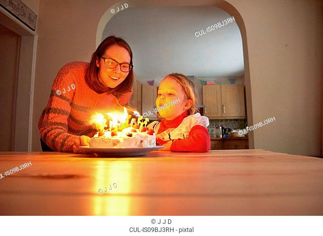 Mother and toddler daughter blowing out birthday candles at kitchen table