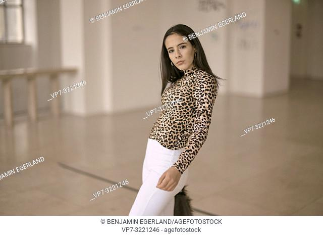 confident woman indoors, fashionable clothing style, in Munich, Germany