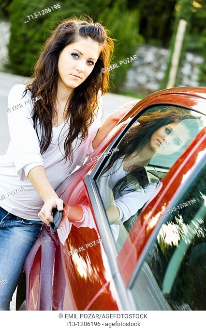 Young woman is opening a door of the car