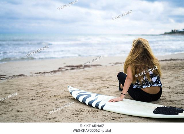 Young woman with siurfboard sitting on the beach looking to the sea