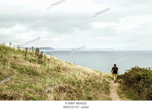 Rear view of a man in walking boots with a rucksack, walking along a coastal path, and a sea view