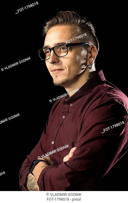 Portrait of man with glasses and arms crossed against black background