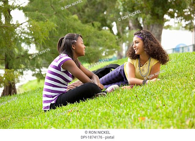 fort lauderdale, florida, united states of america, two teenage girls talking while laying on the grass