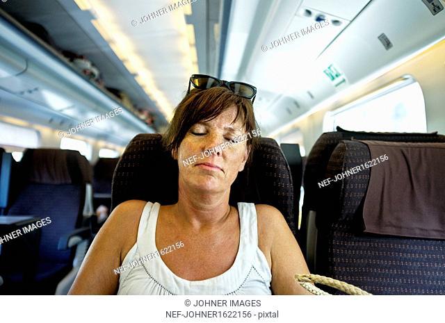 Mature woman sleeping in train