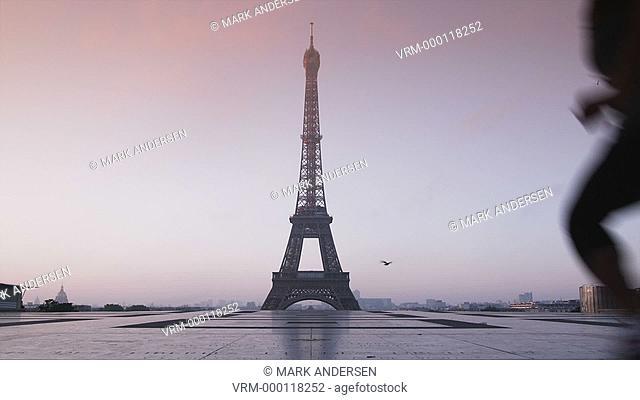 woman running towards the Eiffel tower