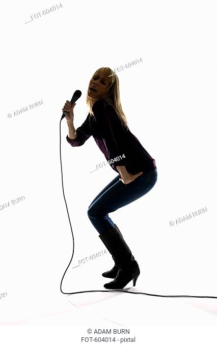 Studio shot of a woman singing into a microphone