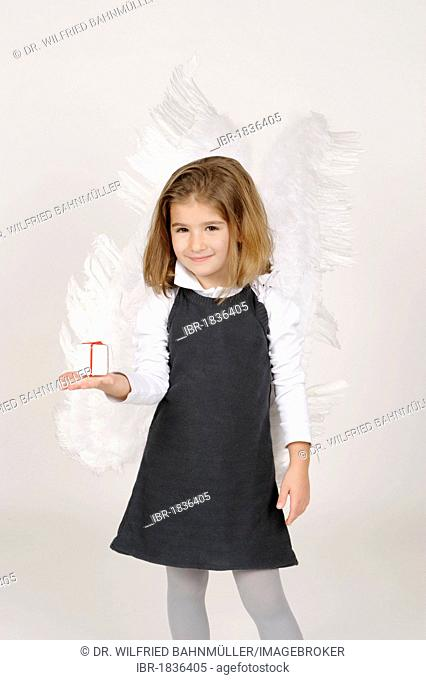 Girl with angel wings with Christmas present