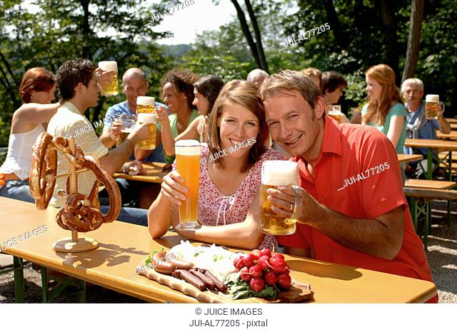 View of a young couple raising their drinks, beergarden, Munich, Bavaria, Germany