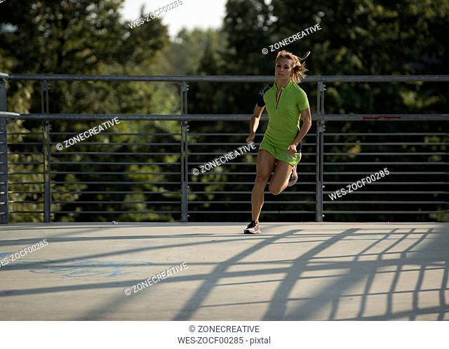 Young woman running on bridge