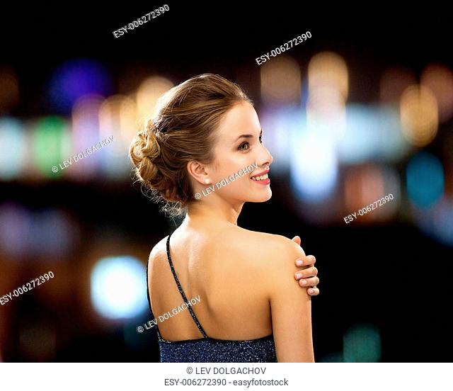 people, holidays and glamour concept - smiling woman in evening dress over black background over night lights background from back