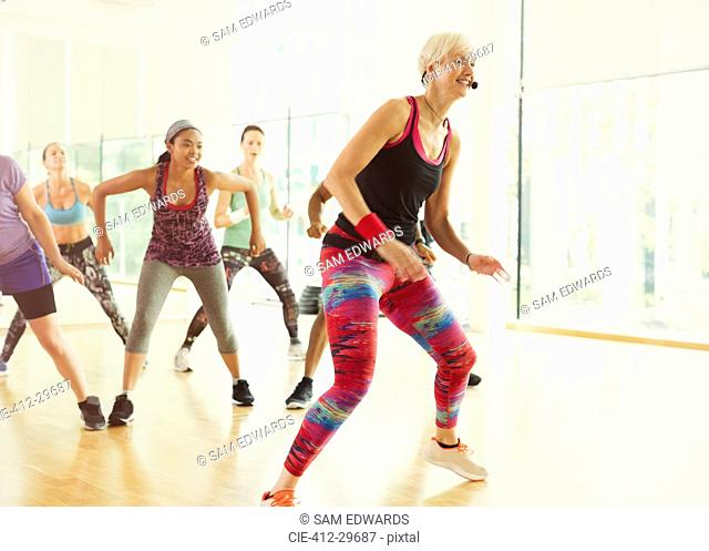 Energetic fitness instructor leading aerobics class