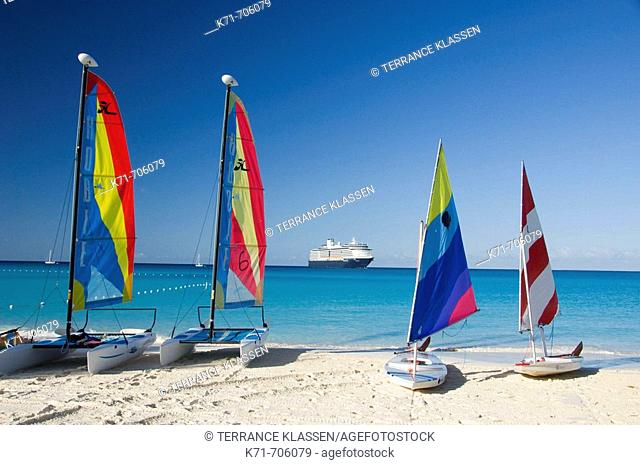 Colorful sails on the beach with the Holland America cruise ship Westerdam anchored offshore at Half Moon Cay, Bahamas, 2008