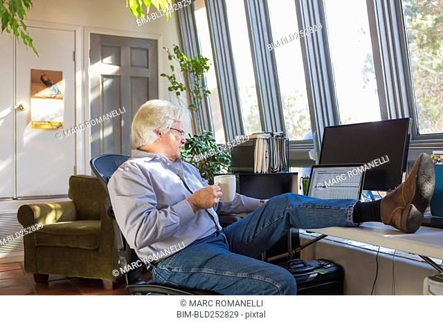 Caucasian man drinking coffee and using laptop with feet up on desk