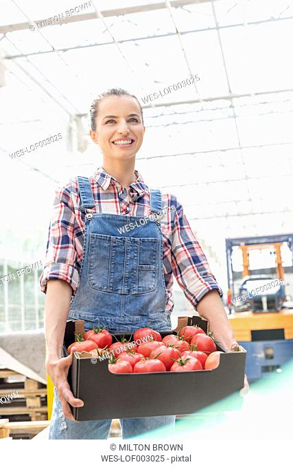 Smiling young woman in dungarees carrying box with tomatoes