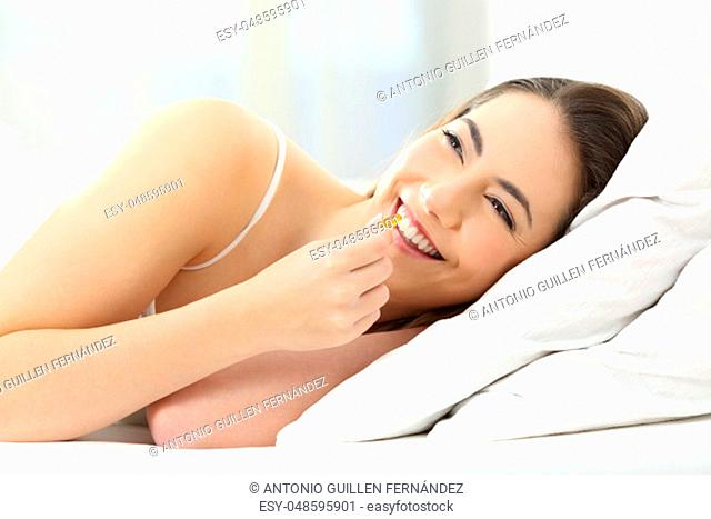 Portrait of a happy girl taking a vitamin supplement pill on a bed at home