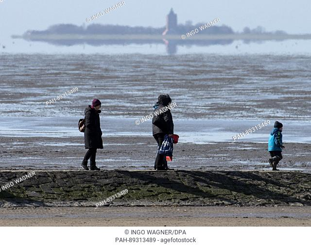Strollers walk along the stone pier at the beach of Cuxhaven, Germany, 25 March 2017. The contours of the Baltic Sea island Neuwerk can be made out against the...