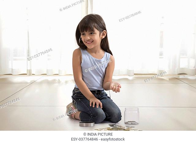little girl with coin box and coins on floor
