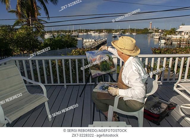 Woman painter painting the Hope Town Harbour. Hope Town, Elbow Cay, Abacos. Bahamas