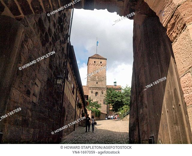 A tower of the Nuremberg Castle as seen through an arched entrance to the Kaiserburg