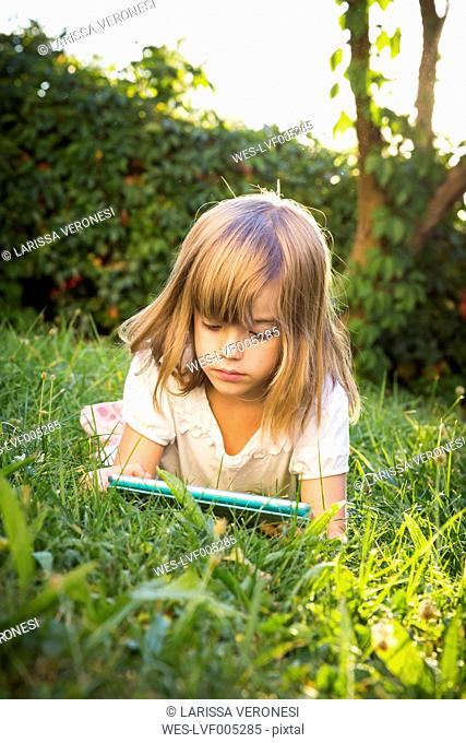 Little girl lying on a meadow using tablet