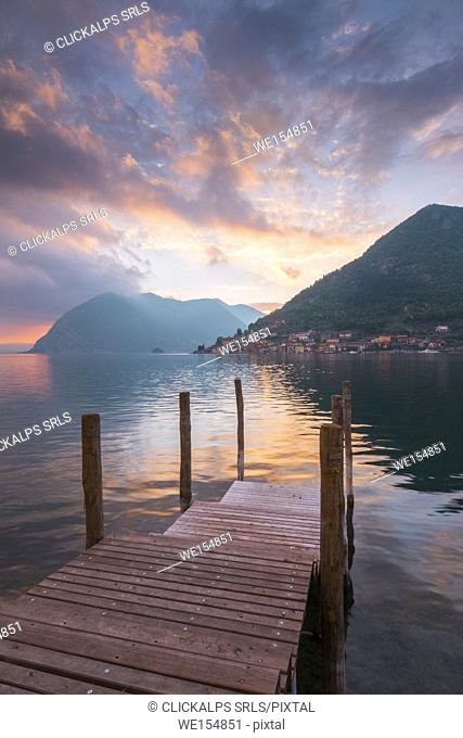 A pier in the lake toward Peschiera Maraglio at sunset, Montisola, Iseo lake, Brescia province, Lombardy district, Italy