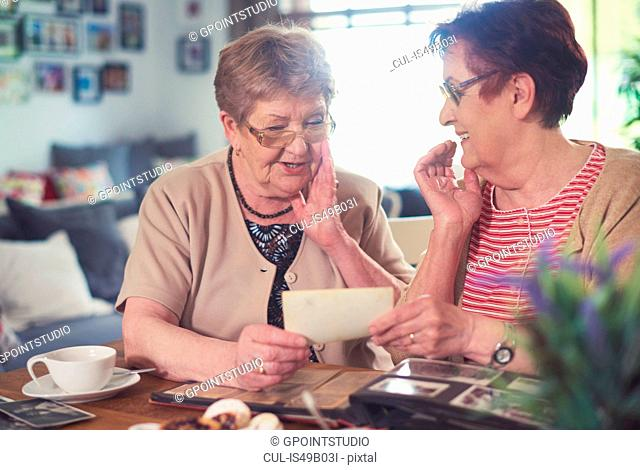 Two senior women chatting while looking at old photographs at table