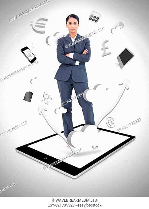 Serious businesswoman with crossed arms on a tablet pc against a digital gray background