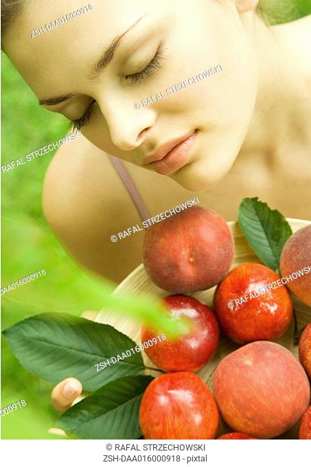 Young woman holding up bowl of peaches and nectarines