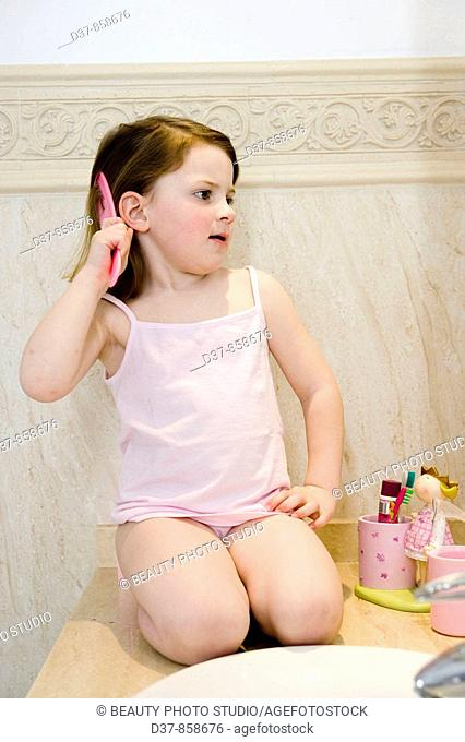 Little girl combing her hair