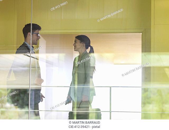Businessman and businesswoman talking in modern office corridor
