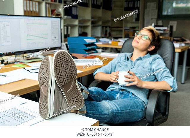 Woman sitting in office with feet up, taking a break