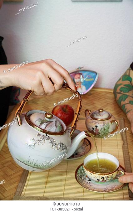 A hand pouring green tea into cup
