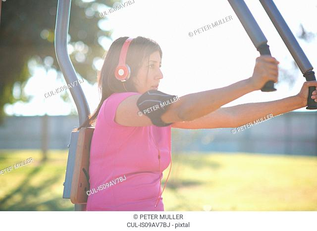 Side view of mature woman wearing headphones using outdoor pec deck