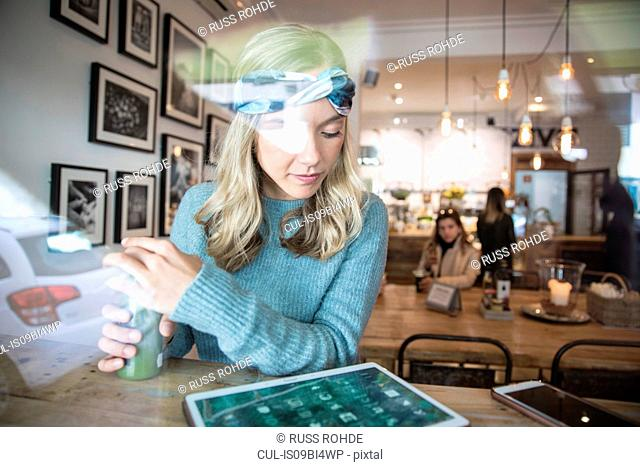 Young woman with vegetable juice looking at digital tablet in cafe window seat