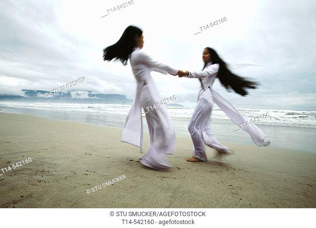 Two schoolgirls in national dress dance on the beach as a tropical storm gathers off Danang's coast. Quang Nam province. Vietnam