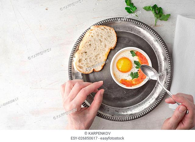 Eating eggs baked with tomatoes and parsley top view
