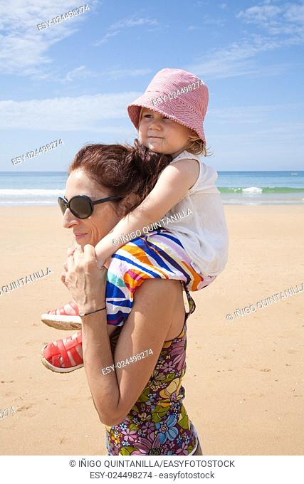 woman mother black sunglasses carrying on shoulders two years old blonde baby with pink hat white shirt and colorful trousers at summer beach