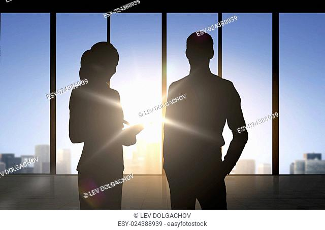 business, partnership, teamwork and people concept - silhouettes of partners over office window background