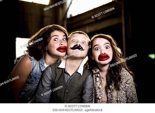 Two Wide-Eyed Girls and Boy Wearing Wax Lips and Making Silly Faces in Abandoned Warehouse
