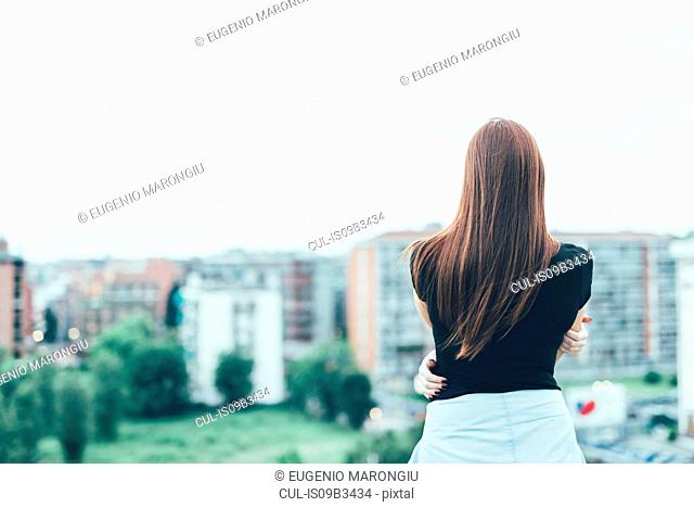 Rear view of young woman with long red hair looking out over cityscape