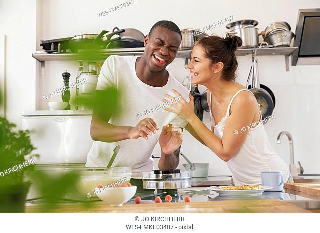 Young couple having fun together in the kitchen