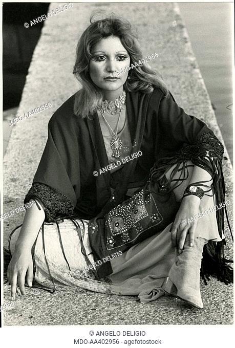 Mia Martini sitting. Italian singer Mia Martini (Domenica Berté) sitting on a low wall. Viareggio, 1970s