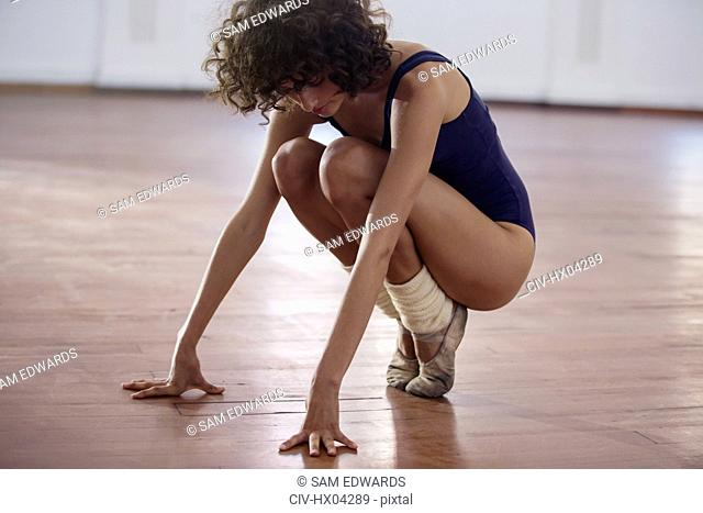 Young female ballet dancer stretching in dance studio