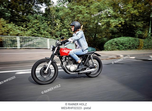 Young woman riding motorcycle on a street