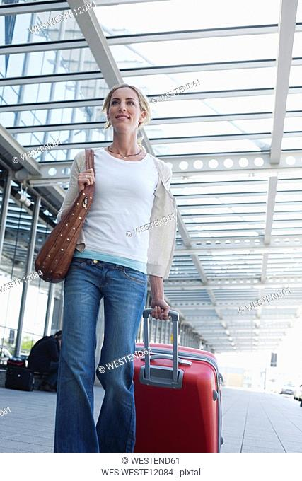 Germany, Leipzig-Halle, Airport, Young woman with suitcase